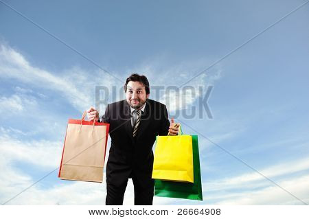 Man with shopping bags against blue sky