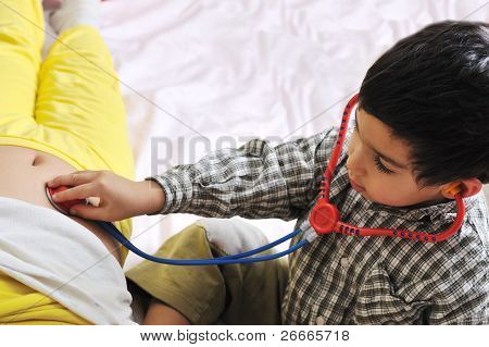 girl & boy playing with doctor's stethoscope toy