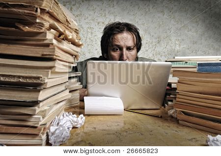 Accountant in problems. Alone working on laptop with a lot of books around on messy table.