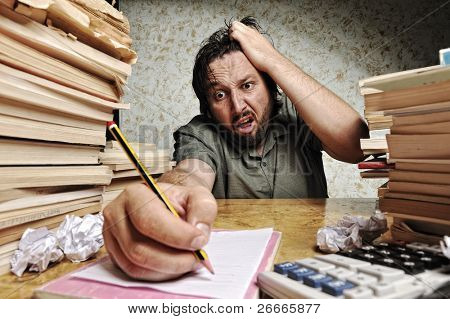 Businessman in problems. Alone working in office with a lot of books around on messy table. Yelling and screaming for bad results.