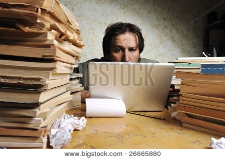 Businessman working in office on laptop. Messy table with a lot of books on.
