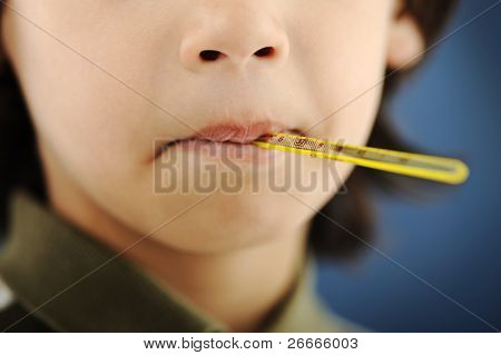 Closeup portrait of an ill boy with thermometer in his mouth, part of face only