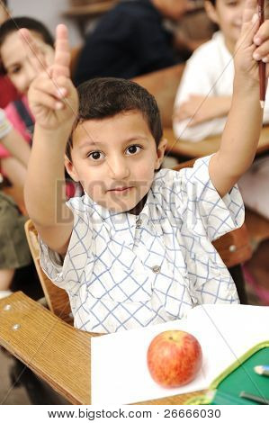 Positive cute kid in the school, rising his hand for answering, red apple in front of him