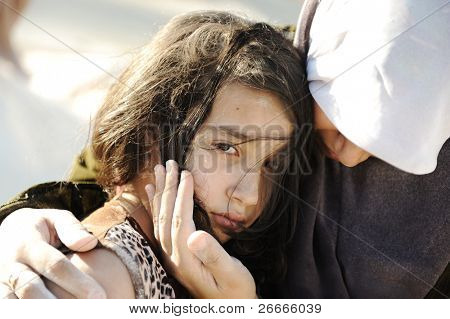 sad abused girl in arms of her mom, gaza - egypt