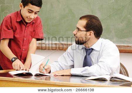 Lehrer, die Schüler im Klassenzimmer Hausaufgaben lösen zu helfen