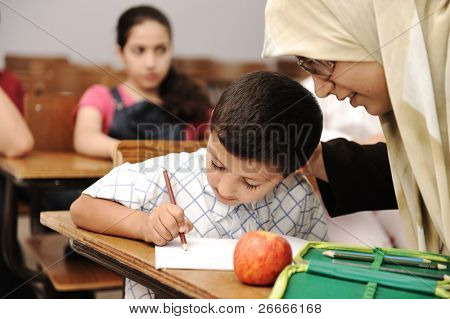 Female Muslim teacher helping a little pupil in the classroom