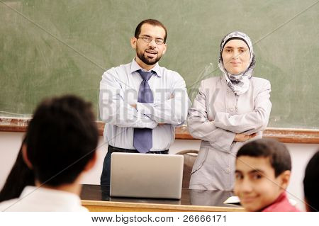 Muslim arabic kids in the school, classroom wit a two teachers