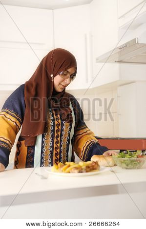 Beautiful muslim woman standing in kitchen