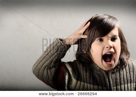 Angry upset child screaming  with hand on his head