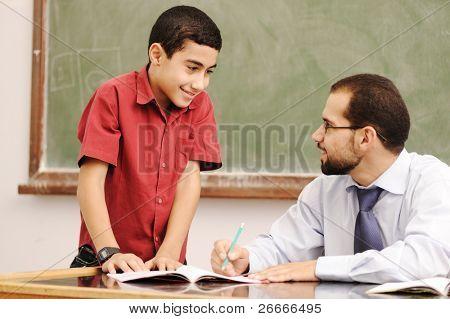 Profesor de ayudar a los alumnos en el aula para resolver tareas escolares