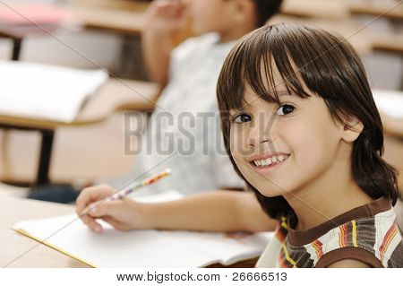 Lindo niño positivo escribir y sonriendo. Interior, escuela, sala de clase.