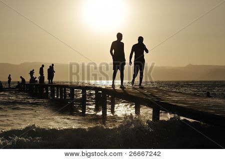 Group of happy young people at the beach on beautiful summer sunset walking on breakwater