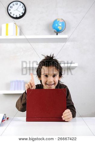 Little happy boy doing homework in his room with white shelves, book on table