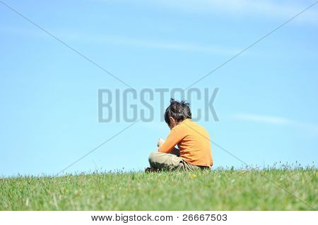 Photo of young boy sitting on the grass  and looking down. He is thinking and sad abandoned lonely
