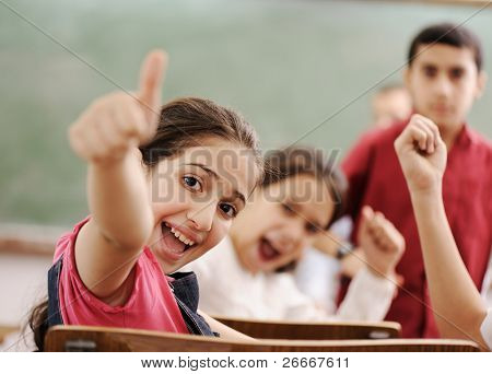 Happy children with their teacher in classroom, doing schoolwork