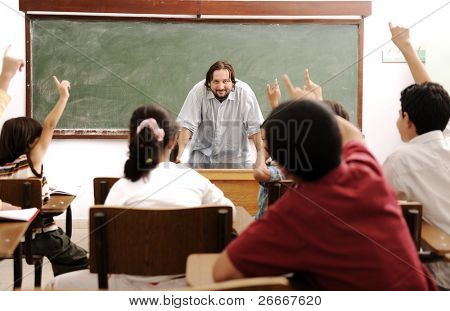 Happy children with their teacher in classroom, doing schoolwork