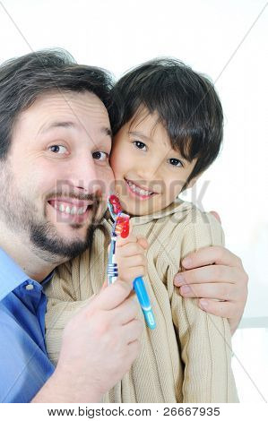 Father teaching his son how to clean teeth