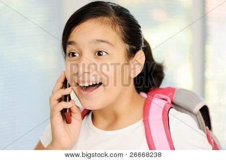 School girl with cell phone, talking and smiling