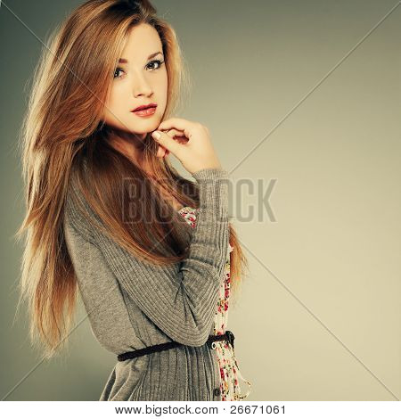 A beautiful young woman is in brown clothes