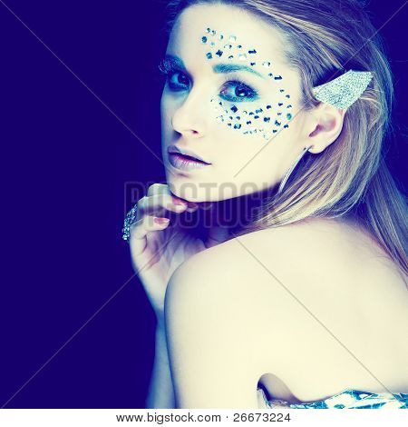 Portrait of a beautiful girl with strasses on face, on a black background