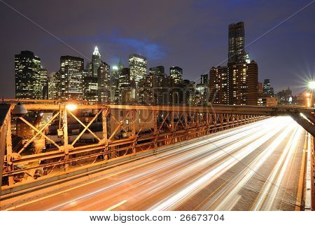 The view of the Financial District in New York City behind traffic on the Brooklyn Bridge.