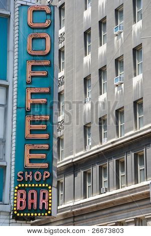 "Retro diner sign in the city saying ""coffee shop bar."""