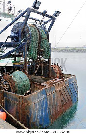 Popa de um barco de pesca com corrico redes em uma chuva fina.