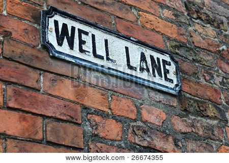 "Road sign on a brick wall reading ""well lane"""