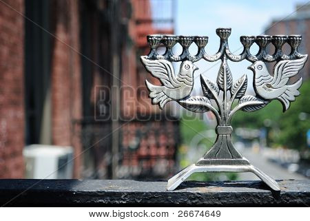 Peace dove menorah on ledge with urban background.