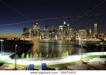 Lower Manhattan at night from the Brooklyn Heights Promenade as a helicopter flies by.