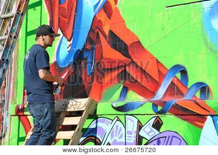 QUEENS - OCTOBER 7: Artist works at Five Pointz, an outdoor exhibit space featuring numerous graffiti artists October 7, 2010 in Queens, New York.