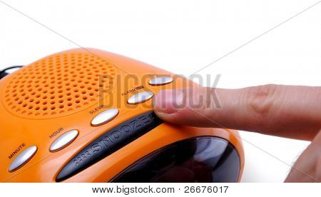 Finger pressing a snooze alarm button