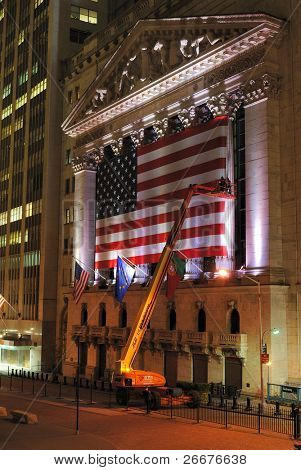 NEW YORK CITY - MAY 26: The historic New York Stock Exchange, one of the largest stock exchanges in the world, illuminated at night while a crane erects the flag May 26, 2010 in New York, New York.