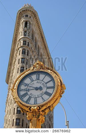 NEW YORK CITY - JULY 3: The Flatiron building with the 5th Ave Building Clock in Manhattan July 3, 2010 in New York, NY. Considered a groundbreaking architectural feat, it was completed in 1902.