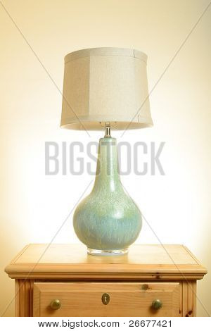 A lamp on a wooden end table.