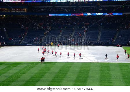 ATLANTA, GEORGIA - JUNE 16: Stadium workers place plastic on the field as rain caused delays during a Braves vs. Mets game at Turner Field on June 16, 2011 in Atlanta, Georgia.