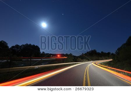 Cars pass on a country road at night