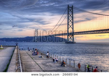 KOBE, JAPAN - JULY 10: Fishermen on the Maiko Park Pier view Akashi Kaikyo Bridge July 10, 2011 in Kobe, JP. With a span of 6,532 feet, the Akashi Bridge is the longest suspension bridge in the world.