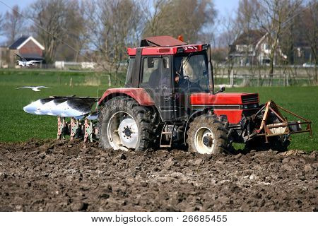 Farmer plows his land with a  tractor