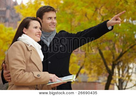 Tourists In Autumn Using City Map