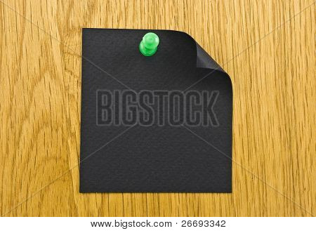 Single black blank note paper attached to a wooden wall