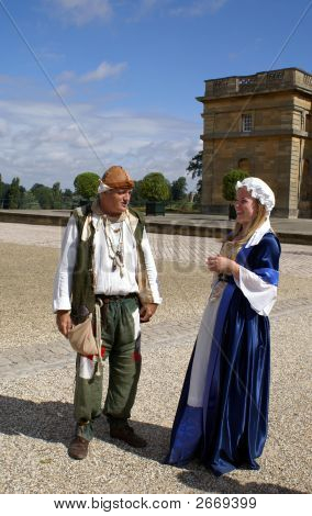 Couple Wearing The 17Th Century Costume Laughing & Talking