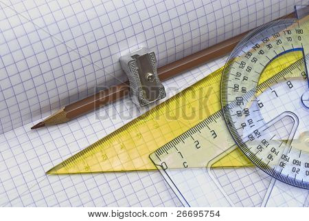 Pencil and sharpener with triangle on  workbook page