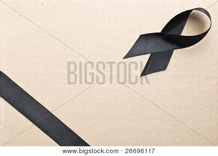 Black ribbons on cardboard background