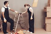 Master Painter. Gray Wall. Cardboard Boxes And Construction Ladder. Man And Woman In Uniform. Master poster