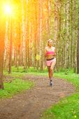 Young woman sports, running in the park. Girl model runs at sunrise or sunset outdoors. Healthy life poster