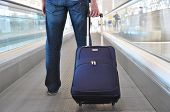 Traveler with a suitcase on the speedwalk poster