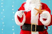 Santa Holding A Toy Airplane And A Starfish On A Shiny Light Blue Background poster