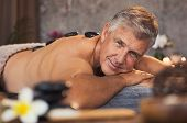 Portrait of senior man with hot stones on massage table looking at camera. Smiling mature man pamper poster