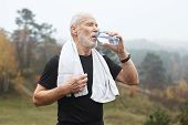 Portrait Of Tired Active Mature Sixty Year Old Man In Black T-shirt Drinking Water From Plastic Bott poster
